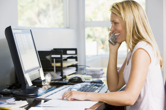 Woman in home office using computer talking on telephone